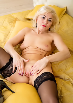 Mature blonde Sylvie shows her body in black lingerie