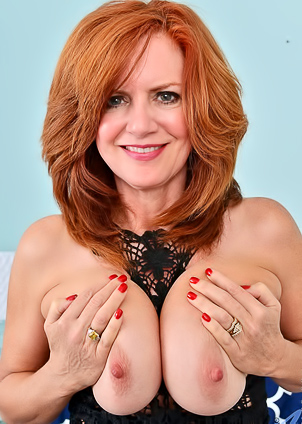 Ginger milf Andi James poses dressed in lace lingerie